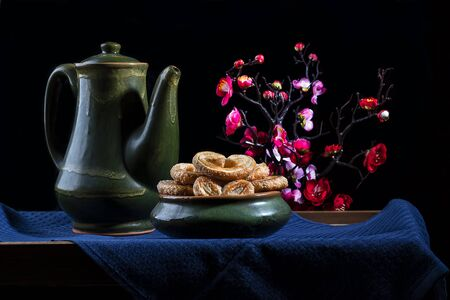 Still life, antique pottery with flowers in the background