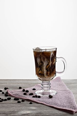 Cold coffee with ice and cream, on wooden background Banco de Imagens