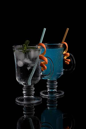 Blue and transparent cocktail, carbonated refreshing cold drink. On a black background