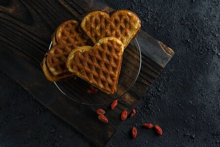 Waffles in the form of a heart on a dark wooden board and a black background with berries Banco de Imagens