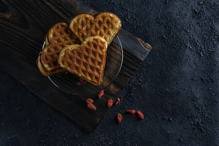 Waffles in the form of a heart on a dark wooden board and a black background with berries. Dessert