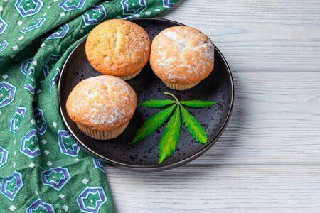 Cannabis and cupcakes with marijuana on a black plate, concept of medical marijuana, home cooking. View from above