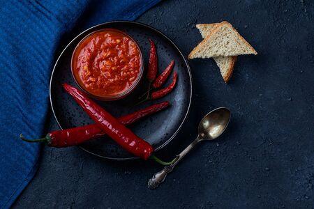 Hot pepper paste and harissa sauce. Adjika on a black background. Traditional Tunisian, Georgian and Arabic cuisine. Homemade pasta harissa. Copy space flat lay, top view. Foto de archivo