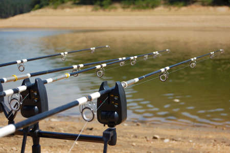 Picture of fishing rods on the waterside of dam lake
