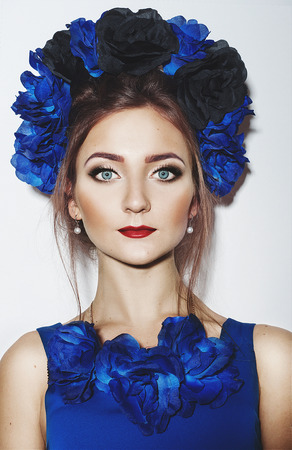 Beautiful young girl with blue flowers wreath and blue dress photo