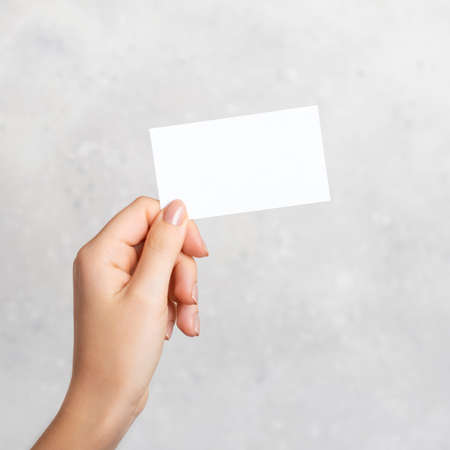 Female hand holding a blank business card, cutaway on gray concrete background with copy space.