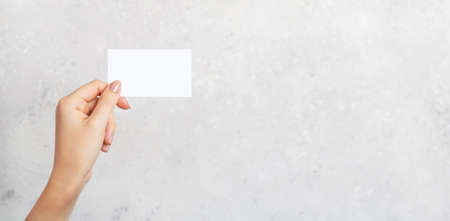 Female hand holding a blank business card, cutaway on gray concrete background with copy space. Branding mockup template