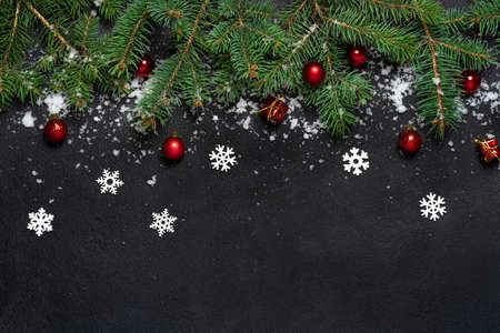 Christmas or New Year decoration background. For fir tree branches on black background with copy space. Flat lay. Pattern. White snowflakes and snow, red balls. Banque d'images