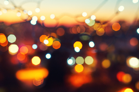 Blurred background of the lights of Christmas garland on the background of a sunset over the city. Bokeh basic background for design