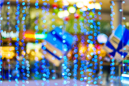 Bright blue Christmas garlands for decorations in the lobby of the mall. Blurred bokeh basic background for design