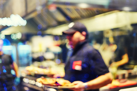 Blurred restaurant tables and chairs in the lobby of the shopping center. The waiter brings pizza to visitors. Open kitchen. Blurred bokeh basic background for design