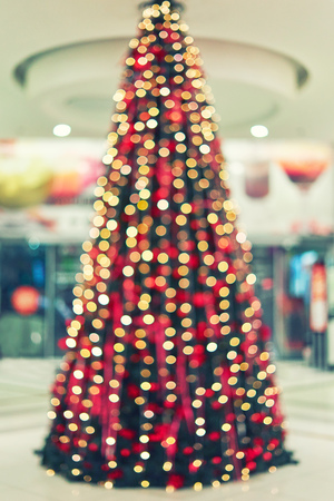 Blurred big bright Christmas tree decorated with colorful garlands and balloons in the lobby of shopping center. Bokeh basic background for design Stock Photo