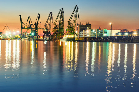 unloading: Evening panorama of the cargo port. Loading and unloading of ships
