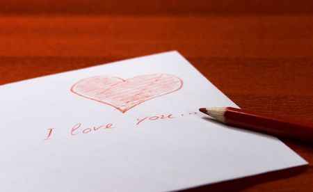 white envelope with red heart and pencil on red background photo