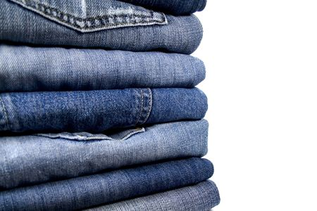stack of blue jeans over white photo