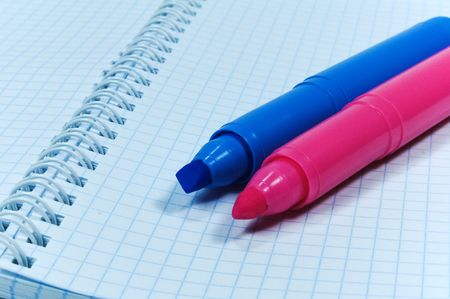 two colored markers over notebook photo