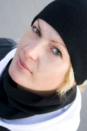 Portrait of the green-eyed blonde in black in cap and scarf photo