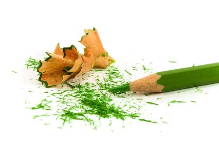 green pencil and sawdust on white background photo