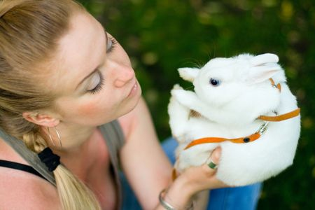 girl with her white rabbit in the park photo