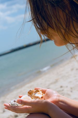 pretty girl at the beach with shells in her hands photo