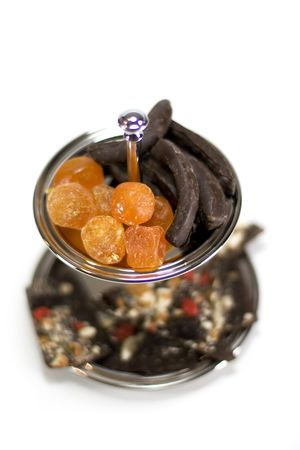 dried fruit and chocolate in a bowl isolated on white background photo