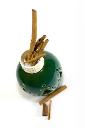 cinnamon sticks in green vase isolated on white background Stock Photo - 3410160