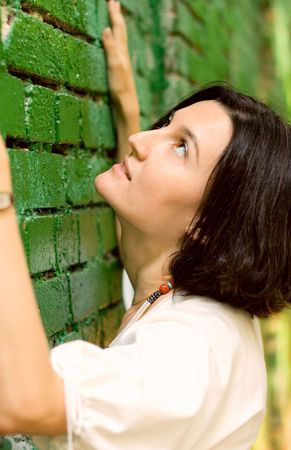 Woman leans on the wall photo