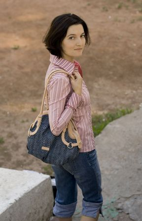 outdoor portrait of pretty brunet woman with bag photo