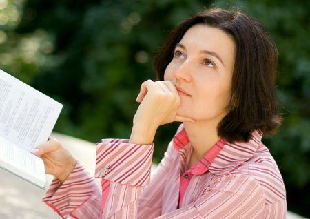 Portrait of brunet woman reading in park photo