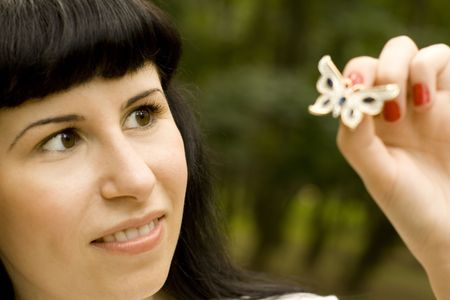outdoor portrait of pretty young brunette with brooch-butterfly photo