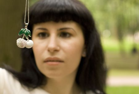 outdoor portrait of pretty young brunette with jewelery cherry. girl out of focus. photo