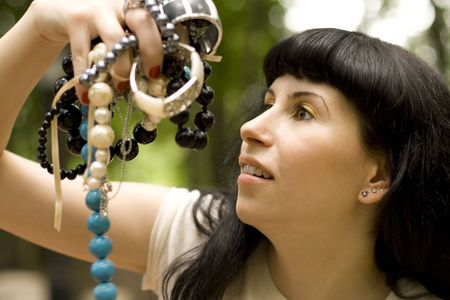 closeup portrait on young brunette holding a lot of beads Stock Photo - 3449657