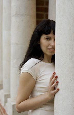 portrait of pretty girl standing near white column photo