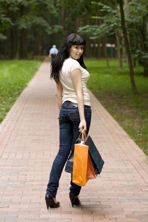 young smiling brunet girl with shopping bags outdoor photo