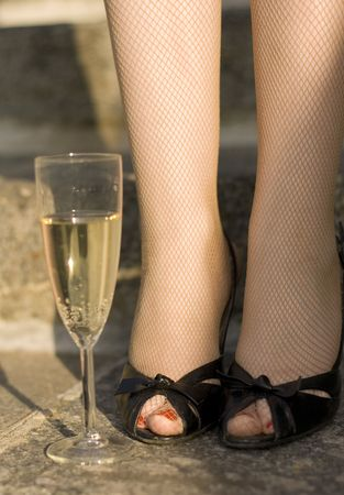 girls feet nd wineglass of champagne on stairs photo