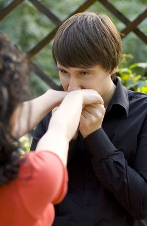 outdoor portrait of young man kissing hands of her gilfriend photo