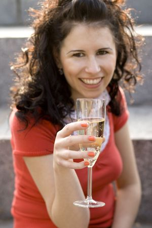 outdoor portrait of smiling girl with champagne glass, focus on glass photo