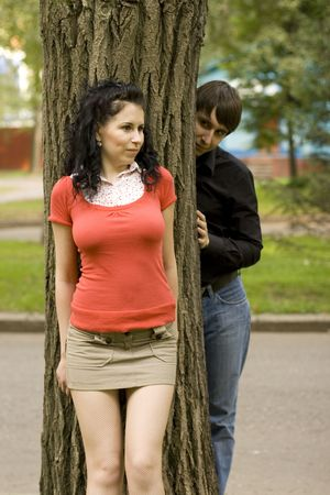 pretty woman and a man hiding behind a tree photo