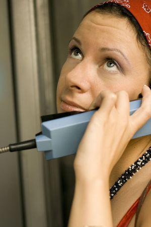 pretty girl having a call on a public telephone photo