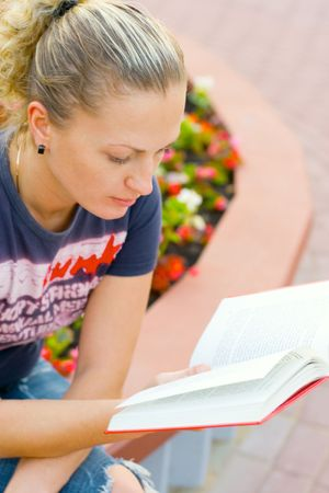 portrait of attractive woman reading in the park photo
