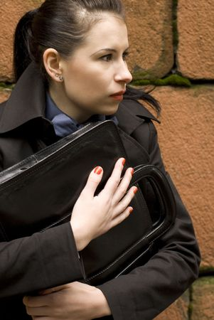 business woman in black holding portfolio near brick wall Stock Photo - 3574976