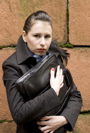 business woman in black holding portfolio near brick wall Stock Photo - 3620688