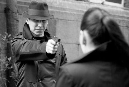 monochrome portrait of man threatens the woman with a pistol Stock Photo - 3643322