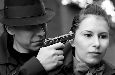 threatens: monochrome portrait of man threatens the woman with a pistol