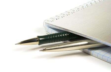 blank notebook and two pens closeup photo