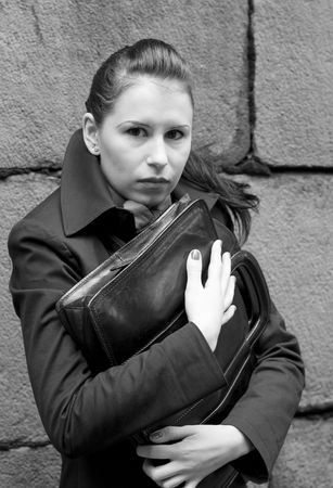 business woman in black holding portfolio near brick wall Stock Photo - 3643329