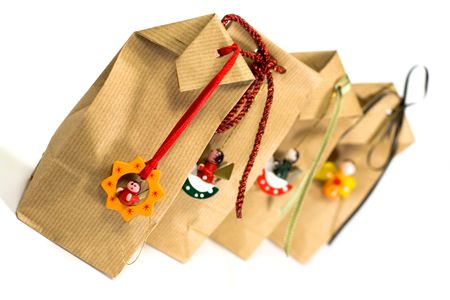 four brown gift bags with decorations isolated on white background photo