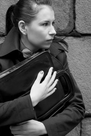 business woman in black holding portfolio near brick wall Stock Photo - 3664300