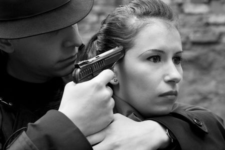 monochrome portrait of man threatens the woman with a pistol photo
