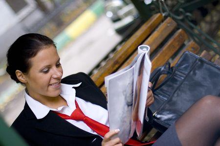 outdoor portrait of smiling businesswoman reading magazine photo